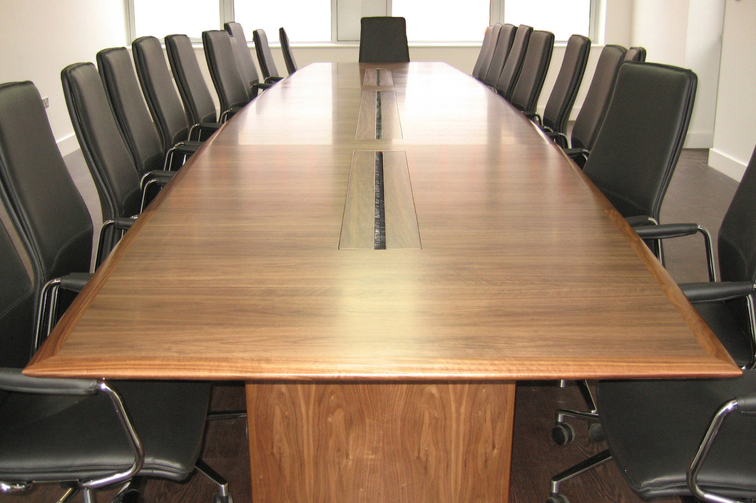Barrel shaped conference table with central cut outs and leather chairs
