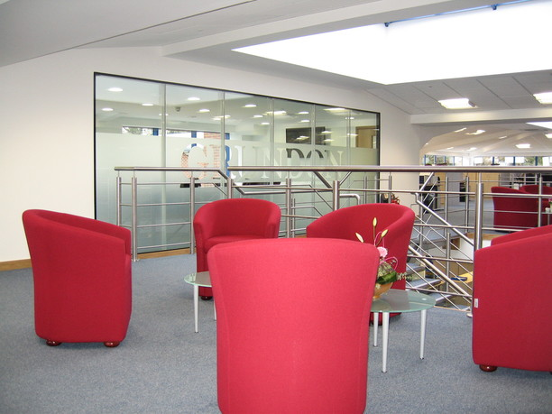 Meeting space with red tub chairs and glass coffee tables