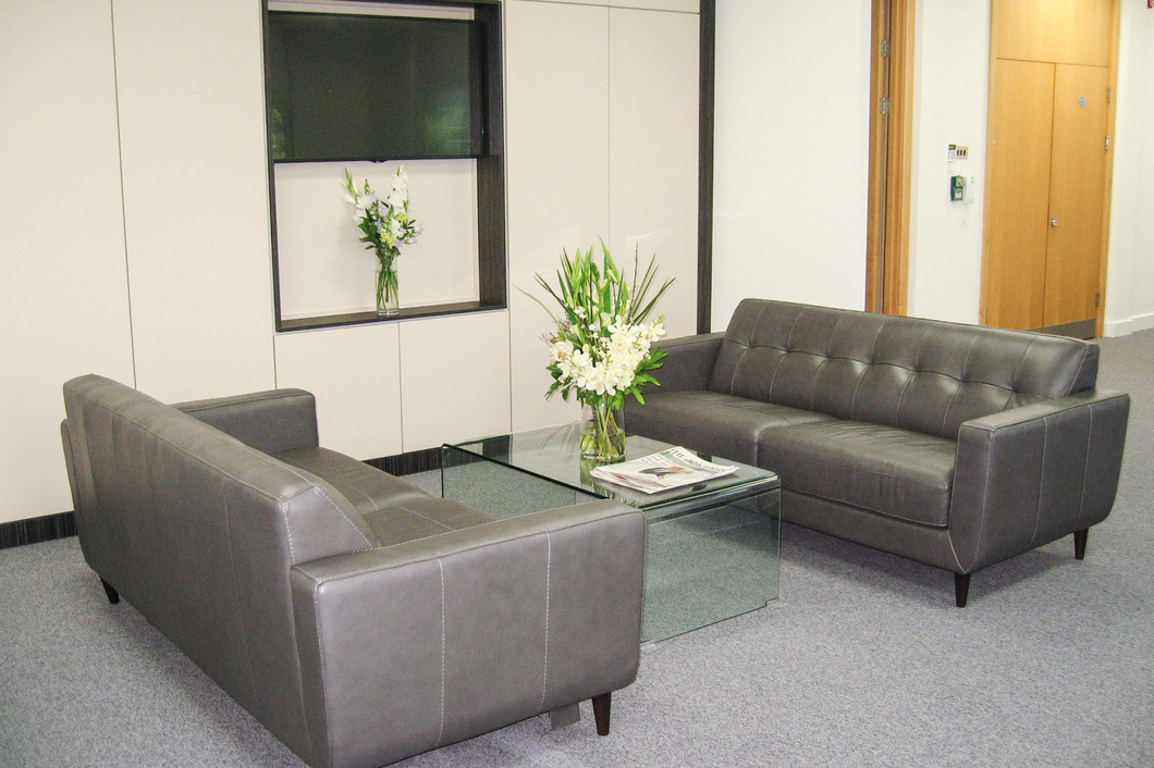 Reception sofas with coffee taable and plasma screen mounted in the floor to ceiling storage