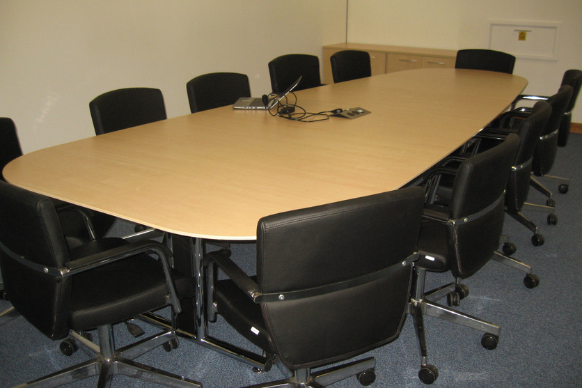 Pear shape conference table with swivel chairs