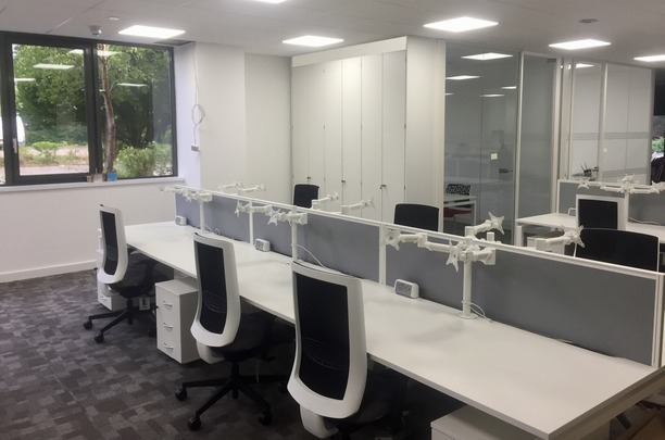Bench desks with mesh chairs, screens, monitor arms and desk power