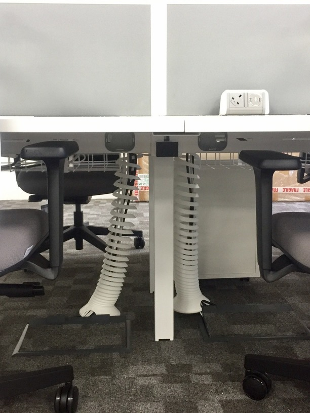 Close up of cable spines, cable trays and desk top power