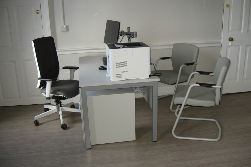 Consulting room with desk, mesh back chair and cantilever visitors chair