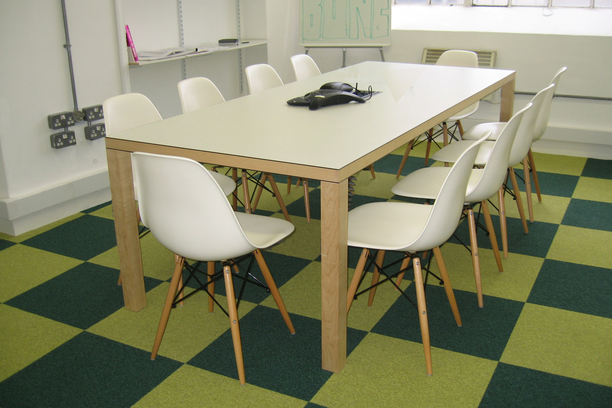 White meeting table with chairs on a green checked carpet tile