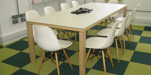 Meeting Room table at Sprinklr with wood frame table chairs and checked flooring